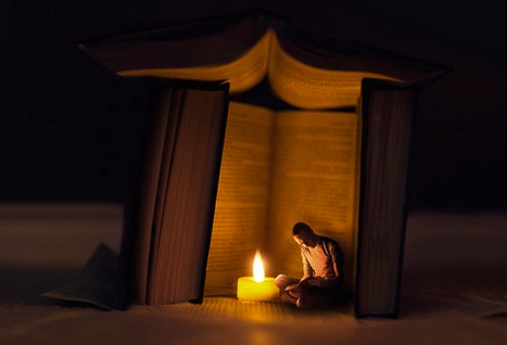 A person reading a book inside a tent made of books