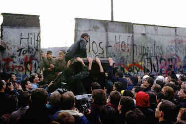 A man sitting on the Berlin wall as it falls, surrounded by a crowd of people
