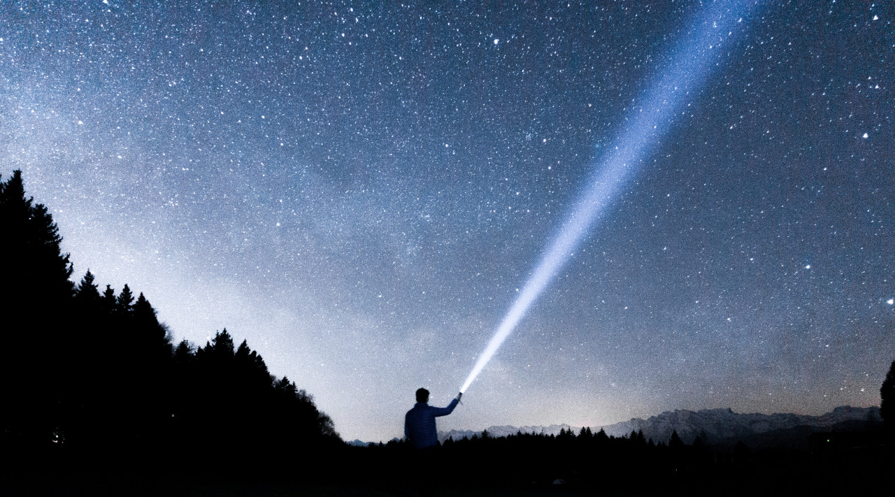 person shining a search light into the night sky